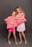 Красивые 2 девушки в розовых пижамах играют перед идти положить в постель Стоковое Изображение