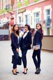 Красивые девушки в черных костюмах представляя на улице Стоковые Изображения RF