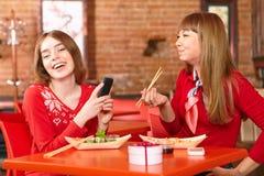 Красивые девушки едят крены суш на баре суш. Стоковые Фото