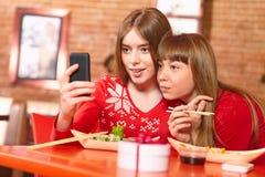 Красивые девушки едят крены суш на баре суш. Стоковое Фото