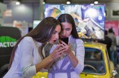 Красивые девушки используют smartphone на выставке 2017 Киева вставляемой Украины Стоковое Фото