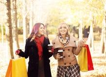 Красивые девушки идя в парк с красочными сумками Стоковая Фотография