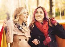 Красивые девушки идя в парк с красочными сумками Стоковые Изображения RF