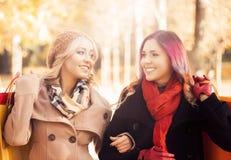 Красивые девушки идя в парк с красочными сумками Стоковые Фото