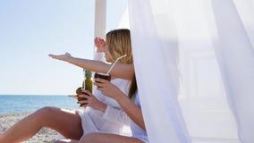 Красивые девушки на бунгале, остатках лета на пляже, ветре развивают белые занавесы, кокос в смеяться над рук акции видеоматериалы