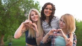 Красивые девушки показывают их влюбленность и делают сердца с их руками Лучшие други совместно сток-видео