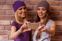 Красивые девушки представляя с устройством Стоковое Фото