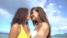 Красивые девушки принимая selfie используя телефон на пляже усмехаясь и закручивая наслаждающся природой на каникулах