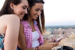 Красивые девушки сидя на крыше и слушая к музыке на su Стоковое фото RF
