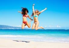 Красивые девушки скача на пляж Стоковое Изображение