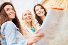 Красивые девушки смотря в туристскую карту в городе Стоковые Фотографии RF
