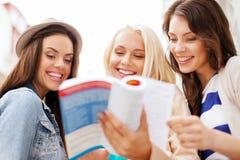 Красивые девушки смотря в туристскую книгу в городе Стоковые Изображения