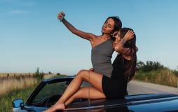 Красивые 2 девушки сфотографированы на дороге Стоковые Изображения RF