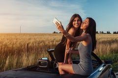 Красивые 2 девушки сфотографированы на дороге Стоковое Фото