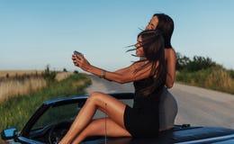 Красивые 2 девушки сфотографированы на дороге Стоковые Фото