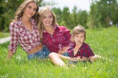 Красивые девушки с мальчиком на траве Стоковое Фото