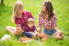 Красивые девушки с мальчиком на траве Стоковое Изображение RF