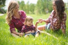 Красивые девушки с мальчиком на траве Стоковая Фотография RF