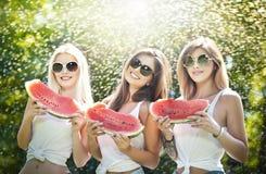Красивые девушки с солнечными очками есть свежий смеяться над арбуза Счастливые молодые женщины держа куски арбуза outdoors Стоковое Изображение
