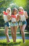 Красивые девушки с солнечными очками есть свежий смеяться над арбуза Счастливые молодые женщины держа куски арбуза outdoors Стоковая Фотография
