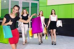 Красивые девушки с хозяйственными сумками приближают к молу Стоковая Фотография
