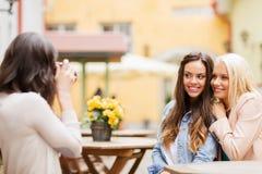 Красивые девушки фотографируя в кафе в городе Стоковые Изображения RF