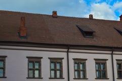 Красивые желтые исторические средневековые европейские здания низко-подъема с щипцом крыши красной плитки и прямоугольными окнами стоковые изображения