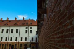 Красивые желтые исторические средневековые европейские здания низко-подъема с щипцом крыши красной плитки и прямоугольными окнами стоковое изображение
