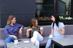Красивые женские друзья смеясь над и говоря на кафе, выпивая кофе Стоковые Фотографии RF