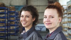 Красивые женские инженеры усмехаясь к камере представляя на фабрике видеоматериал