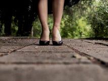 Красивые женские ноги в черных ботинках лакированной кожи на на открытом воздухе плитках стоковые изображения