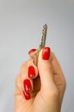 Красивые женские пальцы с красными ногтями держат ключ Стоковая Фотография