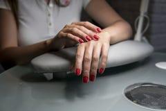 Красивые женские руки с красными ногтями в красоте пригвождают салон Красивые женские ногти и маникюр стоковые фотографии rf