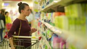Красивые женщины выбирают брызг Тележка супермаркета с продуктами приближает к ей акции видеоматериалы