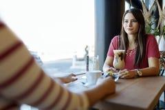 Красивые женщины выпивая кофе и злословить Стоковые Фотографии RF