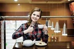 Красивые женщины в чае рубашки шотландки выпивая в кафе Стоковые Фотографии RF