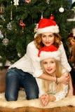 Красивые женщины в шляпах Санты красных лежа около рождественской елки Стоковое Фото