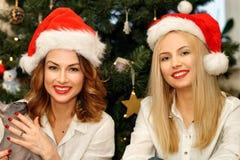 Красивые женщины в шляпах Санты красных на рождественской елке Стоковые Фотографии RF