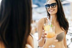 Красивые женщины на пляже наслаждаясь коктеилями Стоковые Фотографии RF