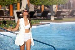 Красивые женщины ослабляя около роскошного poolside стоковое изображение