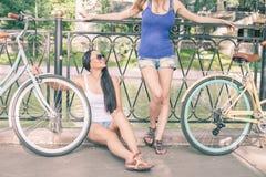 Красивые женщины одели в шортах отдыхая после перемещения велосипедом Стоковое Изображение RF