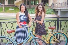 Красивые женщины одели в шортах отдыхая после перемещения велосипедом Стоковое фото RF