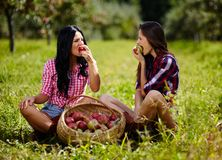 Красивые женщины принимая укус яблока Стоковые Изображения