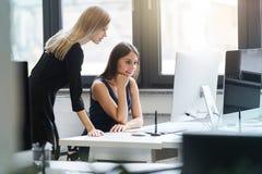 Красивые женщины работая совместно в офисе на компьютере Стоковое Изображение RF