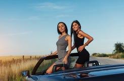 Красивые 2 женщины сидя в автомобиле с откидным верхом Стоковое Фото