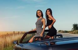 Красивые 2 женщины сидя в автомобиле с откидным верхом Стоковые Изображения RF