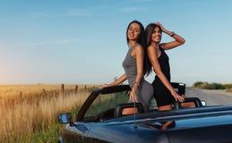 Красивые 2 женщины сидя в автомобиле с откидным верхом Стоковые Фотографии RF