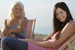 Красивые женщины сидя на Deckchairs на пляже Стоковые Фото