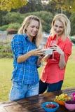 Красивые женщины смотря мобильный телефон Стоковые Фотографии RF