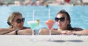 Красивые женщины с коктейлем в бассейне видеоматериал